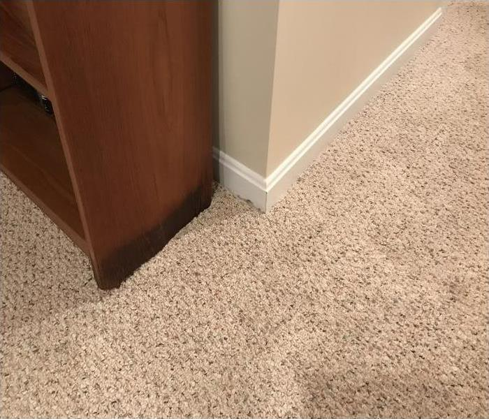 Water damage in a carpet seeping into furniture